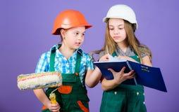 Деятельности при улучшения дома Дети выбирая цвет краски для их новой комнаты Девушки детей планируя реновацию E стоковое фото
