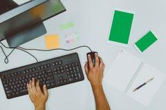 Деятельность бизнесмена путем использование компьютера пока памятка на тетради стоковая фотография