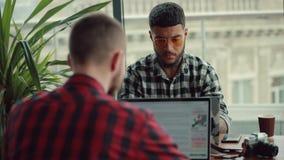 Деятельность молодых людей ведя блог онлайн ноутбуками в кафе делая дело сток-видео