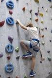 Деятельность скалолазания на искусственной взбираясь стене, кавказском мальчике с линией безопасности стоковые фотографии rf