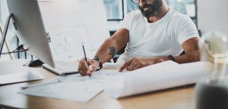 Деятельность стекел глаза бородатого профессионального архитектора нося на современном студи-офисе просторной квартиры с настольн Стоковые Фотографии RF