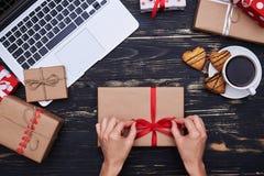 Деланные маникюр руки женщины связывают бабочку ленты на подарочной коробке Стоковая Фотография RF