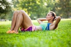Делать девушки фитнеса сидеть-поднимает на парке на траве Стоковая Фотография