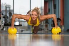 Делать женщины нажимает вверх тренировку на желтых шариках Стоковые Изображения RF