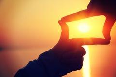 Делать из рук против яркого захода солнца моря Стоковые Фото