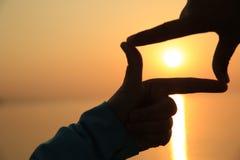 Делать из рук против яркого захода солнца моря Стоковые Фотографии RF