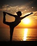 Делать йогу на заходе солнца Стоковые Фото