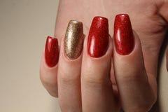 Делать красный цвет ногтей обширно яркие и цвет золота Стоковая Фотография