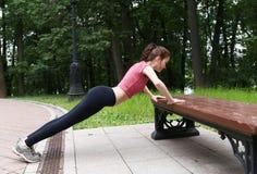 Делать маленькой девочки нажим-поднимает на стенде outdoors в после полудня Стоковая Фотография RF