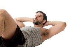 Делать одежд привлекательного латинского человека спорта нося идущий сидит вверх или хрустит Стоковое Фото