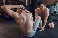 Делать подходящих людей сидеть-поднимает на циновках тренировки на фитнес-клубе Стоковое Фото
