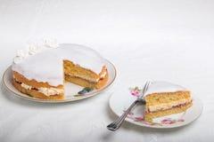 Делать торты губки, распространение торта с вареньем/заповедником и buttercream и замороженный с белыми ручной работы розами на в Стоковое фото RF