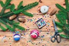 Делать шарик рождества прикалывая sequins на шарик Стоковая Фотография