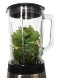 Делать smoothies в blender с зелеными листьями и avocad шпината стоковая фотография