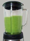 Делать smoothies в blender с зелеными листьями и avocad шпината стоковое фото