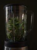 Делать smoothies в blender с зелеными листьями и avocad шпината стоковое изображение