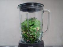 Делать smoothies в blender с зелеными листьями и avocad шпината Стоковое фото RF