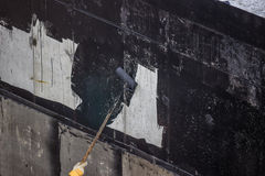 Делающ водостойким, бетонная стена картины работника внешняя с смолкой i Стоковая Фотография