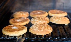 Делающ и жарящ плюшки гамбургера с сезамом на угле зажарьте Стоковое фото RF