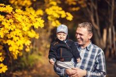 Дед держа его внука на руке, осени Стоковое Изображение