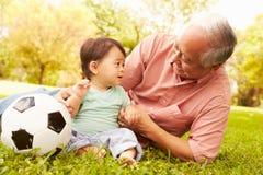 Дед и внук играя с футболом в парке Стоковое фото RF
