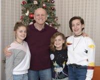 Дед и 3 внучки стоя перед рождественской елкой Стоковое фото RF