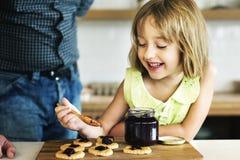 Дед маленькой девочки печет концепцию печенья стоковое фото