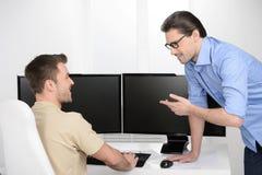 Деловая беседа. 2 жизнерадостных бизнесмена говоря о бушеле Стоковые Изображения RF