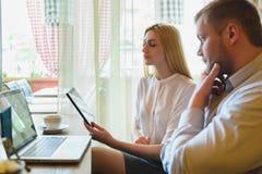Деловая встреча в кафе Человек и женщина смотря компьтер-книжку Стоковые Фото