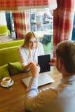 Деловая встреча в кафе человек показывает таблетку к удивленной женщине Стоковые Изображения RF