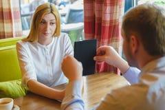 Деловая встреча в кафе человек показывает таблетку к удивленной женщине Стоковые Изображения