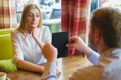 Деловая встреча в кафе человек показывает таблетку к удивленной женщине Стоковое фото RF