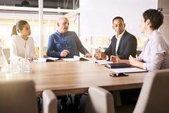 Деловая встреча между 4 наивысшая мощность, расово разнообразные, эклектичные индивидуалы стоковое фото