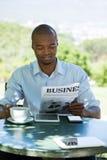 Деловая газета чтения бизнесмена на ресторане Стоковые Изображения
