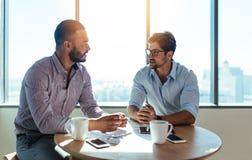 Деловые партнеры обсуждая бизнес-планы сидя на таблице внутри Стоковые Изображения