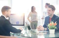 Деловые партнеры обсуждая в конференц-зале с их коллегой Стоковое фото RF