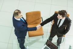 Деловые партнеры рукопожатия около настольного компьютера, в просторном офисе Стоковое фото RF
