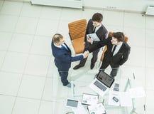 Деловые партнеры рукопожатия перед рассмотрением нового финансового согласования Стоковые Изображения