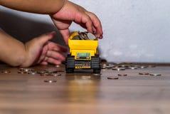 Дело и концепция денег - руки ребенк держа тележку с полным телом монеток Стоковые Изображения
