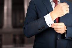 Дело и концепция офиса - элегантный молодой бизнесмен моды в костюме сини/военно-морского флота касаясь на его запонках для манже Стоковые Изображения