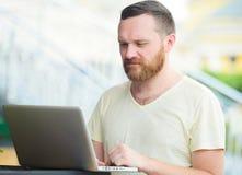 Дело и свобода Человек с бородой за компьтер-книжкой в городе, освобождает стиль, современное дело Стоковая Фотография RF