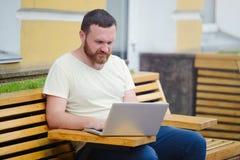 Дело и свобода Человек с бородой за компьтер-книжкой в городе, освобождает стиль, современное дело Стоковое фото RF
