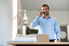 Дело успешного предпринимателя говоря на телефоне в офисе Стоковая Фотография