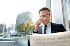 Дело читая газету говоря на телефоне Стоковое фото RF