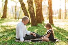 Дед при девушка играя шахмат стоковая фотография rf