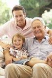 Дед при сын и внук смеясь над совместно на софе Стоковое Изображение RF