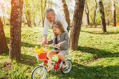 Дед с велосипедом катания девушки Стоковые Фото