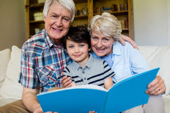 Деды и внук держа книгу в живущей комнате Стоковые Фотографии RF