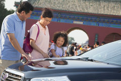 Деды и внучка стоя рядом с автомобилем и смотря карту Стоковые Фото