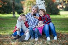 Деды при внуки сидя совместно и делая selfie с мобильным телефоном в парке Стоковые Фотографии RF